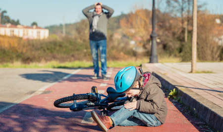 Boy in the street ground with a knee injury screaming after falling off to his bicycle Archivio Fotografico