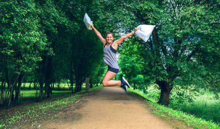 Happy girl jumping with trash bags after doing plogging