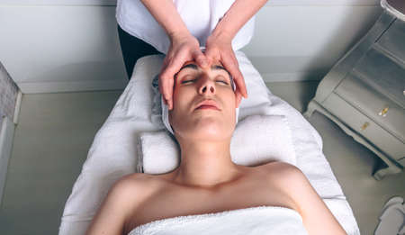 Young woman with closed eyes receiving facial massage on a clinical center. Medicine, healthcare and beauty concept.