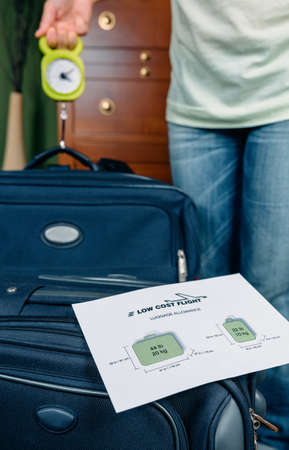 Woman checking hand luggage weight using a steelyard balance by low cost airlines restrictions