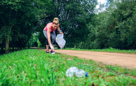 Girl crouching with bag picking up trash doing plogging Foto de archivo