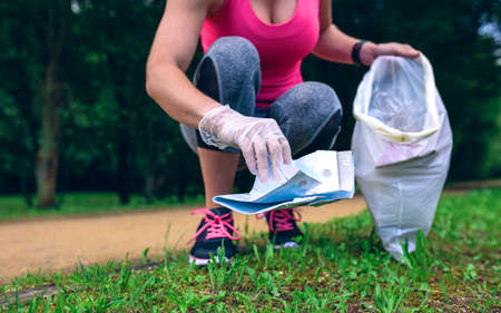 Unrecognizable girl crouching with bag picking up trash doing plogging