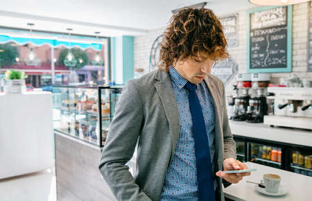 Businessman looking at mobile standing in a cafe