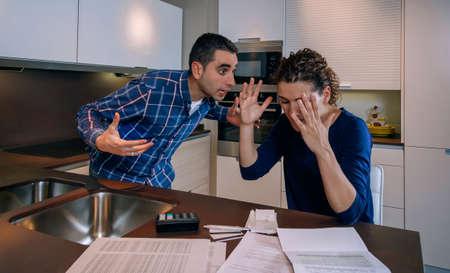 Jeune couple en colère criant dans une dure querelle par leurs nombreuses dettes à la maison. Concept de problèmes familiaux financiers.