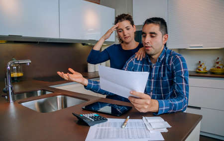 Unemployed young couple with many debts reviewing their bank accounts. Financial family problems concept. Stockfoto