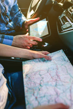 Young couple comparing a paper map and a gps navigator on the tablet sitting in the car
