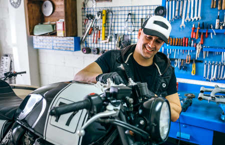Happy mechanic cleaning a customized motorcycle in his workshop