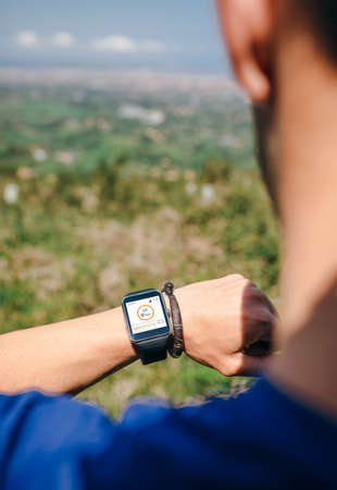 Unrecognizable sportsman looking at a smartwatch outdoors