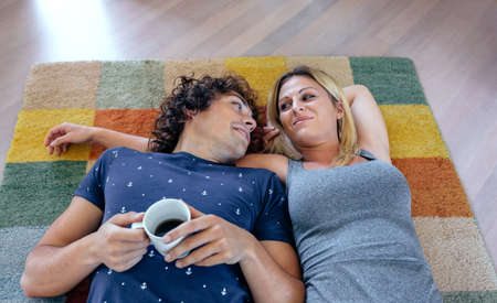 Couple resting lying on the carpet of their new house
