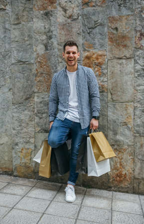 Happy young man with shopping bags leaning on a stone wall