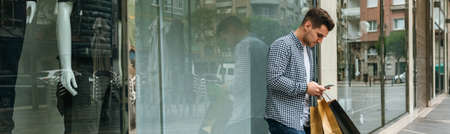 Young man with shopping bags looking mobile leaning on a shop window