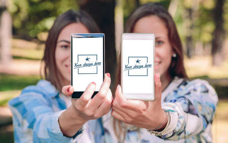 Women friends showing smartphones with their selfie photos taked over a forest background. Customizable mobile screens