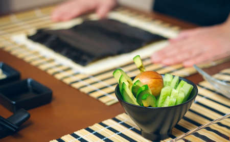 Detail of bowl of avocado cut with chefs hands in the background ready to cook sushi Imagens