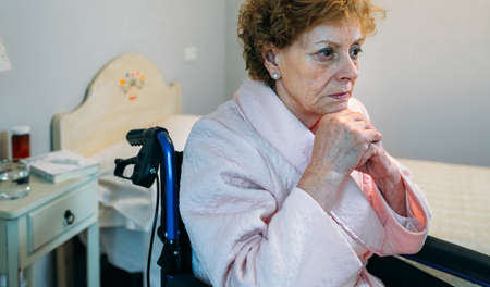 Senior woman in a wheelchair alone in a room Stock fotó