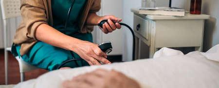 Female caregiver checking blood pressure to a senior woman at home Banco de Imagens