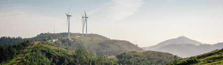 Mountain landscape on a sunny day with wind turbines generating electricity in the background. Nature and ecological energy production concept.