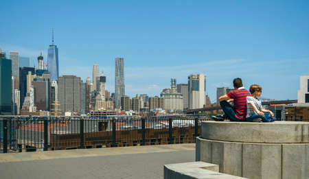 Man and boy with sunglasses sitting in front of Manhattan skyline, in New York City 写真素材