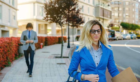 Serious businesswoman walking down the street towards her work while a businessman walks behind. Selective focus on woman in foreground