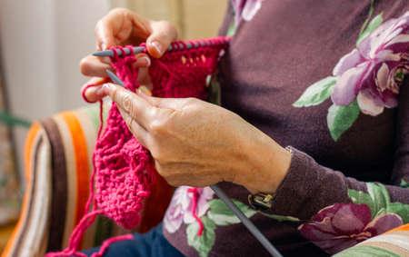 Mani di una donna anziana che lavorano a maglia un maglione di lana a casa Archivio Fotografico