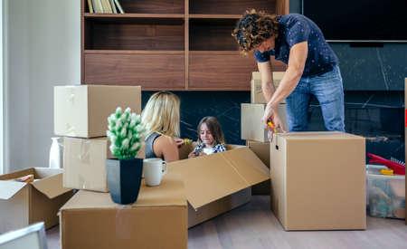 Madre e hijo jugando sentados dentro de una caja en movimiento mientras el padre desempaca