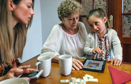 Little girl asking permission to her mother to continue playing the tablet with her grandmother