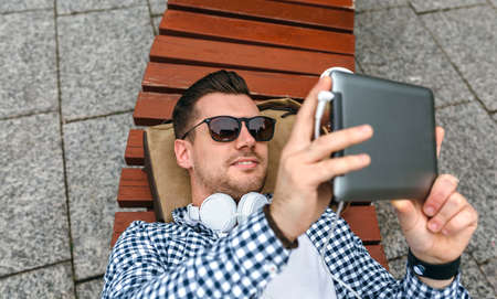 Young man using tablet lying on a park bench outdoors Imagens