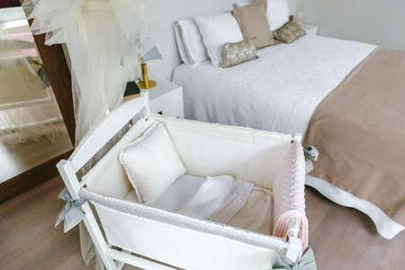 Camera sobria ed elegante con lettino a baldacchino e letto matrimoniale. Messa a fuoco selettiva sul lettino in primo piano