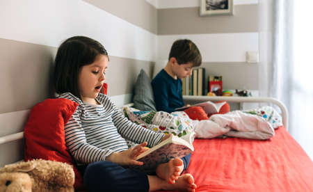 Girl and boy reading a book each sitting on the bed. Selective focus on girl in foreground Stockfoto