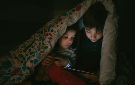 Brother and sister sitting on the bed looking at the tablet in the dark
