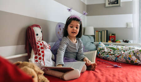 Little girl disguised as a butterfly sitting on the bed teaching her doll to read