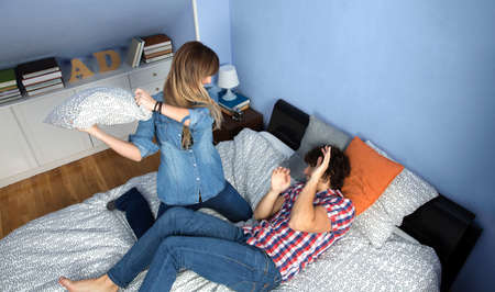 Top view of young couple making a pillow fight on the bed