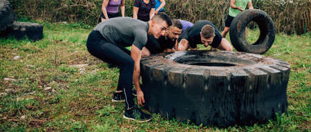 Group of participants in an obstacle course turning a truck wheel