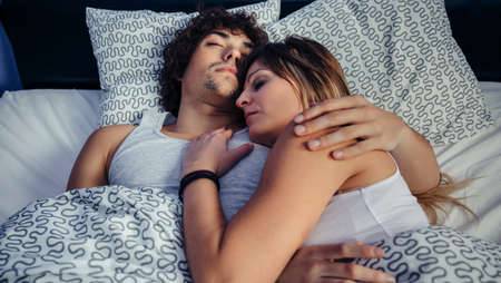 Young couple sleeping embraced in bed at home