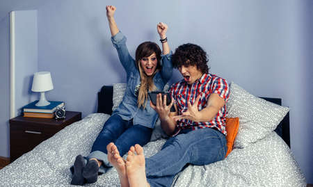 Young couple celebrating victory watching sport on the tablet sitting on the bed