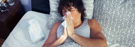 Young man sneezing and covering nose with tissue lying on bed. Sickness and healthcare concept. Stock Photo