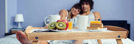 Healthy breakfast served on a wooden tray ready to eat and a happy couple in love hugging in the background. Healthy food and home lifestyle concept. Reklamní fotografie