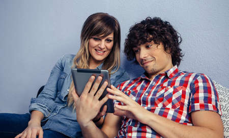 Young couple looking at the tablet sitting on the bed