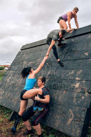 Groupe de participants à un parcours d'obstacles escaladant un obstacle pyramidal