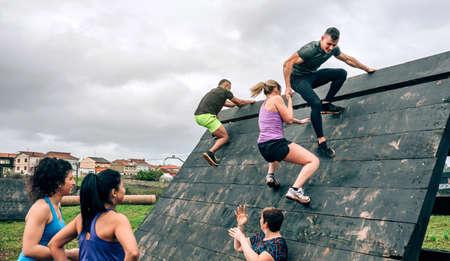Gruppo di partecipanti a un percorso a ostacoli che scala un ostacolo piramidale