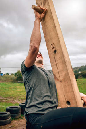 Male participant in a obstacle course doing pegboard obstacle