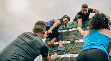 Group of participants in an obstacle course climbing a net 免版税图像 - 120024198