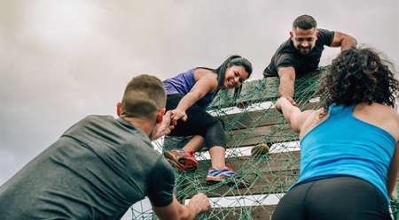 Groupe de participants à un parcours d'obstacles escaladant un filet Banque d'images