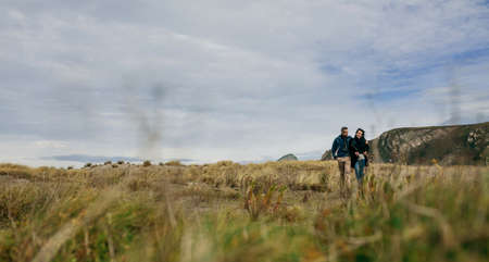 Young couple embraced taking a walk near the coast