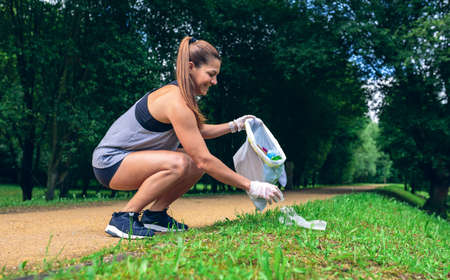 Girl crouching with garbage bag doing plogging outdoors Archivio Fotografico