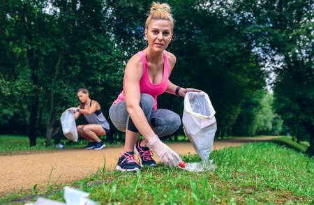 Girl crouching with bag picking up trash doing plogging with friend in background