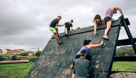 Group of participants in an obstacle course climbing a pyramid obstacle