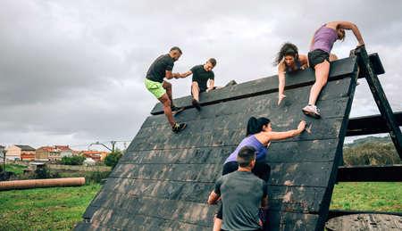 Groupe de participants à un parcours d'obstacles escaladant un obstacle pyramidal Banque d'images