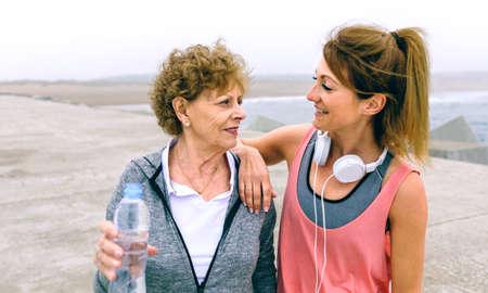 Senior sportswoman talking with female friend by sea pier