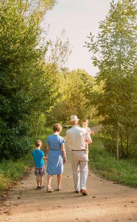 Rückansicht von Großeltern und Enkelkindern, die auf einem Naturweg gehen Standard-Bild