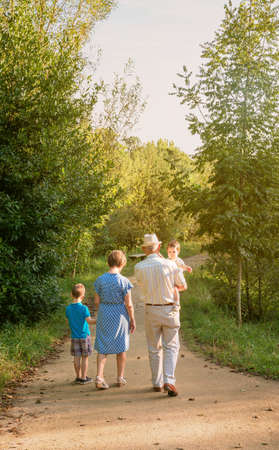 Vista posterior de abuelos y nietos caminando por un sendero natural Foto de archivo